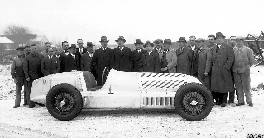 The directors, the engineers and the workers of the racing department with the new Mercedes-Benz W 25 750-kg formula racing car, February 1934.